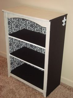 I stole this idea from someone else's pin! I found the bookshelf at an antique store. I glued fabric on the back, painted the bookshelf and shelves black and white, and found a cheap stamp at hobby lobby for the sides! SO FUN!!