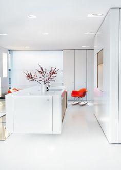 Overalt i lejligheden er der tænkt indbyggede skabe ind for at sikre det rene, minimalistiske look. Skabene bag den orange Eames-gyngestol rummer fx alt børnenes legetø