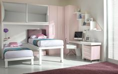 This pink and white girls' room compacts two beds, a desk, storage, and closet space all in one small space with little girl-appropriate design.