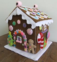 I Love Buttons By Emma: Felt Gingerbread House (I'm thinking it could be made so that it slides down over a box, cut to shape and at the end of the season, fold both of them up and store away.  Make the roof as a separate piece with cardboad inside it like a pillow that folds in the middle.)