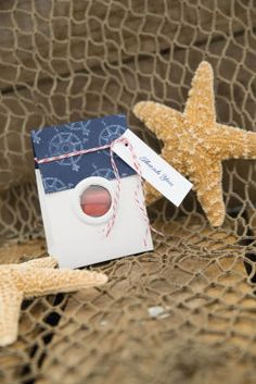 Michaels.com Wedding Department: Nautical Favor Box For this look, add grommets and a custom stamped or patterned paper border to the Gartner Studios white handle favor box. Add the candy, wrap the top with baker's twine and add a Thank You tag. Use other Michaels nautical elements to help accent the table. Courtesy of Gartner Studios®