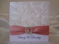 A folded invitation with embossed paper, satin ribbon trim and large A grade diamante buckle.  www.invitationsbysarah.com.au