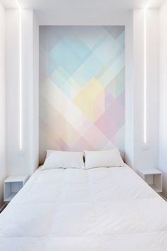 Beautiful white bedroom design with colorful wall in a minimalist apartment in Rome, Italy