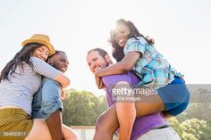 Stock Photo : Men carrying girlfriends piggyback outdoors