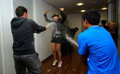 Maria Sharapova is sprayed with champagne as she makes her way to the locker room. What a fitting beverage to celebrate a French Open win!