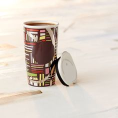 Ornamented with vibrantly colored rectangles, shiny silver elements, and a brown dot, this coffee mug has the look of stained glass art. 2014 Dot Collection.