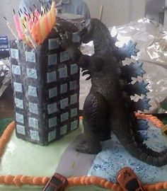 Building shaped cake with Godzilla action figure. I like the use of candles as flames on the building.