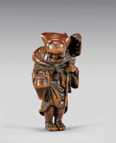 Japanese carved wood figural netsuke; of a an elderly man with a staff and basket, a small monkey on his shoulder, with some inlaid details to backs of legs