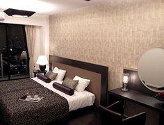 B160重厚感/濃茶の重厚感あるファニチャーがベージュ系のカーテンと壁面クロスに映えて。ボルスターの色とベッドカバーの柄が、アクセントに。