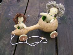 How cute is this!!! ...MKL... gourd pull toy with fiber stuffed dolls. beaded eyes and throw pillow trim hair.