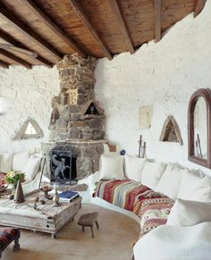 villa in Greece ♥  built-in sofa mostly white but blanketed in color, a low, rustic table on wheels, and a large rock fireplace to ward off the evening's chill  // via 79 Ideas