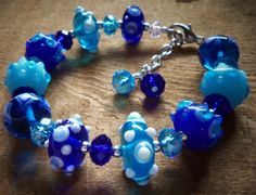 "Blue and Turquoise Bumpy Lampwork Bracelet with Austrian Crystal and matching earrings  It features lovely Blue & Turquoise Bumpy lampwork beads with matching earrings. Beads include different shades of blue and white bumps on some of the beads.  Austrian crystals and sterling silver beads. All the beads are strung on heavy, high quality stainless steel wire and added a good lobster claw closure.  The bracelet is a wearable 7.5"" long, includes ""extender"" to fit most any size wrist. $22 for…"