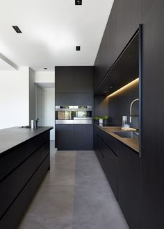 kitchen space features blacked out custom cabinetry with a black kitchen island that allows for seating and serving.