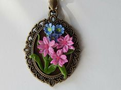 Pink and blue flower on bronze colored pendant necklace.
