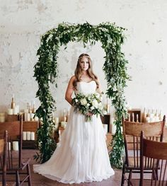 You don't need to spend a bunch of money on flowers to have an enchanting wedding ceremony arch. Layer your arch with different leaves, ivy, baby's breath and a few white roses here and there. This option was used for an indoor wedding and goes well with the plain walls and simple decor.