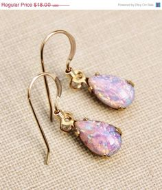 Lovely glass opal earrings made using vintage glass opals from the 1950s. Each opal is pear shaped and is set in an american made, raw brass