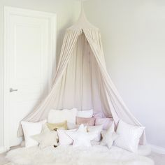 pink canopy with pillows in girl room
