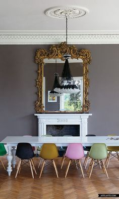 Colorful modern chairs in a traditional dining room.