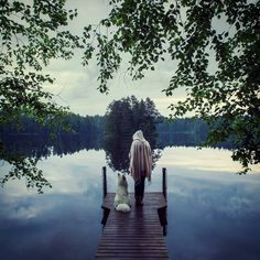 """Reader Suvi Keiju sent us this magical moment -- """"me and my arctic samoyed dog standing by a silent lake on a midsummer night in Saimaa, Finland""""! Photo by Sanna Kaitakari"""
