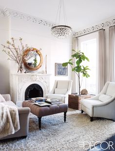 The living room features linen-upholstered armchairs by Mitchell Gold + Bob Williams, a rug by Shaw Floors, and an Ochre light fixture; Deary built the side table and mirror from reclaimed wood, and the tufted ottoman and Hugo Guinness drawing are from John Derian Dry Goods. - ELLEDecor.com