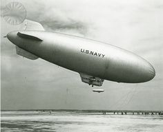 """Right side view of a Navy K type airship during landing. Groundcrew run to grab mooring lines hanging from the nose. """"PATROL OVER - A large U.S. Navy blimp settles slowly earthward after an anti-submarine patrol while a sister ship cruises past in the distance. The big lighter-than-air ships are based near Elizabeth City, N.C."""" November 2, 1942...Credit: unknown (Smithsonian Institution)"""