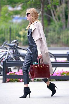 Olivia Palermo in leather overalls, classic duster, Dior boots and crocodile Hermès Birkin bag.