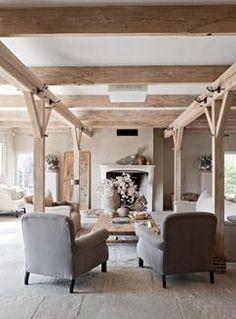 Mooie, sfeervolle, landelijke woonkamer met zithoek gecreëerd tussen de houten balken. Laag plafond, open haard en stoffen meubels zorgen voor extra sfeer.
