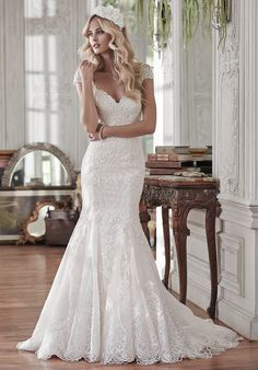 Lovely in lace, this fit and flare wedding dress is the epitome of beauty with…