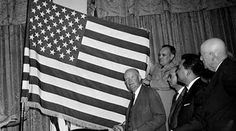 The above photo, which has been scanned to digital for preservation, shows President Dwight Eisenhower holding the newly adopted 50-star flag. It was designed in 1958 by Robert Heft, a 17-year-old high school student from Ohio. In response to an assignment to create something based on an original concept, Heft disassembled his grandparents' 48-star flag, and created the 50-star design now in use, featuring five rows of six stars, alternating with four rows of five stars.