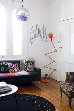 Front room.  Skull cushion is from a label Nicola and Orlando used to sell called 'The Rise and Fall'.  Orange lamp by French brand – Jielde, Kente cloth armchair.  Photo – Jason Busch, production – Lucy Feagins / The Design Files.