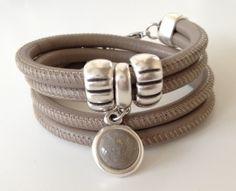 Prachtige dubbele armband van stitched leer die 2 keer om de pols gaat. Met mooie DQ metalen schuivers en een hanger met gekleurde inzet.