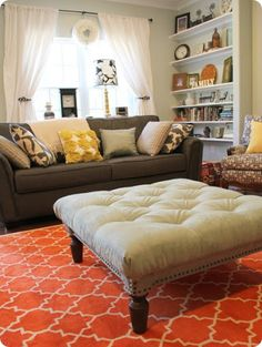 I love the bright orange floor, the bookshelves and the different pillows! Ottoman super cute, and a DIY link for it