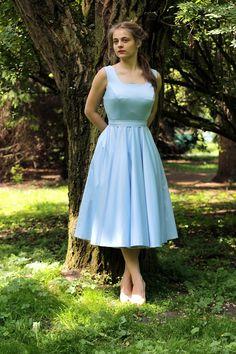 Sukienka Lana uszyta z lekko połyskującej błękitnej tkaniny. To bardzo pracochłonny fason, do