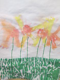 De kleuters tekenden met groene stift stengels of bloemen. Daarna legden ze stukjes crêpe-papier daarop. Als laatste een strook groen crêpe-papier als gras. Daarna alles met de plantenspuit nat gespoten en na een paar minuutjes het crêpe-papier eraf halen. Nutsschool Maastricht