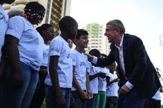 O presidente do COI, Thomas Bach, cumprimenta as crianças refugiadas do Coral…