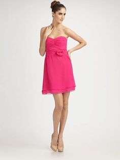 This silk, strapless frock exudes feminine charm in soft ruffles and a demure rosette.