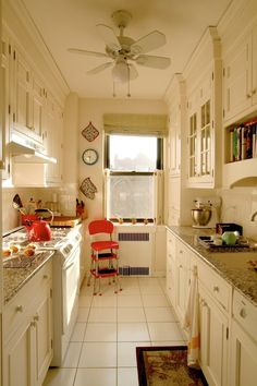galley kitchen layout in white with crown molding via Apartment Therapy
