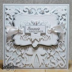 "As white and sparkling as a new fallen Christmas Eve snow, Designer Loretta Lock created this stunning elegant holiday card with beautiful layers of other dies for that ""WOW!"" factor. The lucky recipient will be receiving not only a holiday greeting but an eyeful of wonderful details. Other Supplies: Silver Paint Pen; Silver Cord; Patterned Paper; Light Grey Cardstock; Sentiment Stamp"