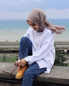 Hijab styles 462533824230607914 - Image may contain: 1 person, sitting, child, ocean, outdoor and water Source by