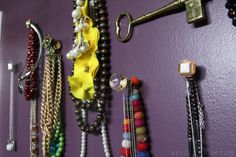 Necklace holders: Nails in the wall with vintage buttons, brooches, drawer-pulls, etc. hot-glued to the nailhead!