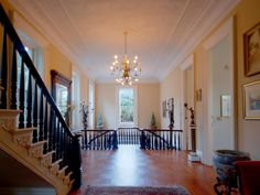 From the floor to the ceiling, the welcoming entryway in this Charleston mansion is appointed in fine woodwork and elegantly refined touches.