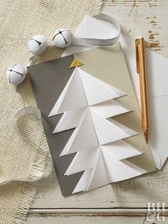 This chic DIY Christmas card wows thanks a simple folding technique. To make, cut white paper into ten 3-inch squares. Cut gold paper into a small triangle. Fold squares in half diagonally, touching opposite corners. Then fold the square in half again, touching corners to form a triangle.  Attach each triangle onto the card with glue, creating the tree shape. Note: Make sure the fold is in the middle to give the card a 3-D effect. Glue the gold triangle at the top of the tree.