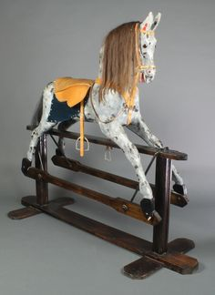 """Lot 459, An early 20th Century dappled grey rocking horse on a treadle base, with mane, tail and leather tack 52""""h x 61""""l x 23""""d, est  £400-600"""