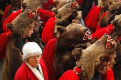 """A woman walks past people performing a traditional """"bear dance"""" in the northeastern Romanian region of Moldova on Dec. 30, 2013. The New Year's parade is a ritual that dates back to pre-Christian times, when dancers would tour villages to ward off evil spirits."""