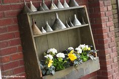 Indoor shelf moved outside on a porch to display flowers and a vintage funnel collection via Inspired by Charm