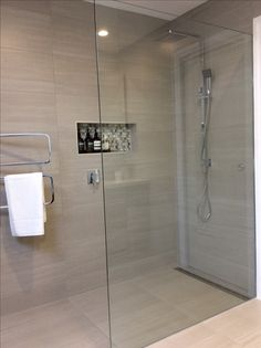 Mosaic tiled niche, rain shower head with hand held spray.  Vertical Swivel towel rail.
