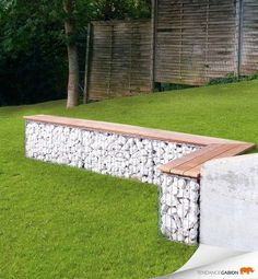 modern garden edging idea of aluminum fencing filled with rocks and topped with a seating bench