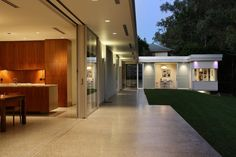 """The home is adjacent to a park and the residents wanted to seamlessly bridge the interiors and exteriors. The concrete floors extend underneath the deep eaves and sliding glass doors open up the interior space, making the home feel larger than its 2,300 square feet.  Bud Brannigan, the home's architect, is known for designing art galleries and takes some of the sensibilities he uses for those spaces and employs them in residential design. """"Like a gallery, the design of our home emphasizes…"""