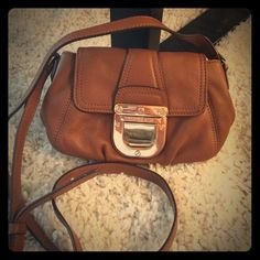 Michael kors cross body purse Tan Michael kors cross body purse small. Gently used, small wear to the front buckle, leather in good condition. Michael Kors Bags Crossbody Bags