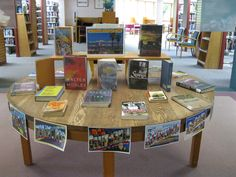 California Here We Come We have this large table that I love using for displays.  I found a bunch of vintage postcards and enlarged them to decorate the sides of the table - this side is filled with fiction about or takes place in California.  Steinbeck and Raymond Chandler have been flying off the table. I figure I can keep this table stocked for a while.